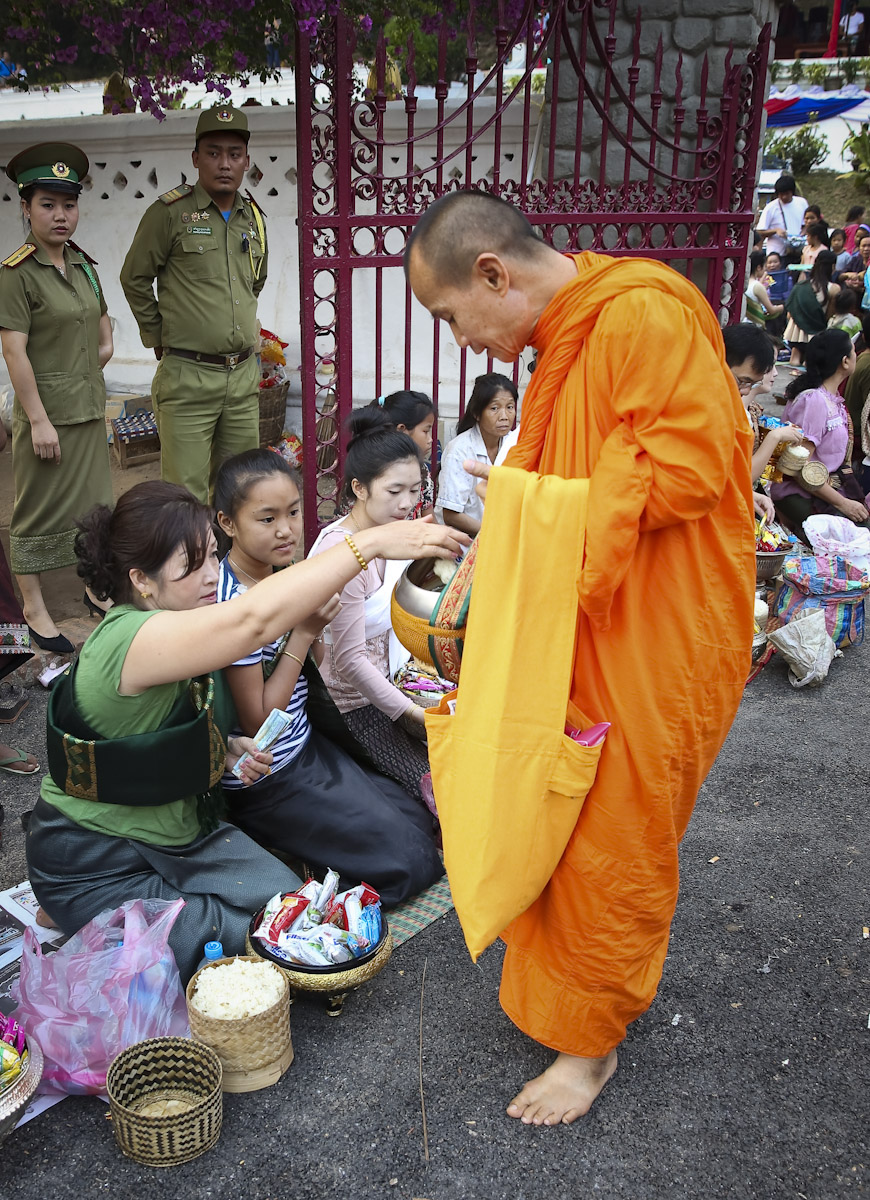 Locals participating in alms giving ceremony in front of National Stadium, Luang Prabang , Laos