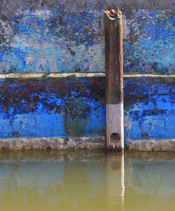 Blue Wall, dirty water and rotting pole