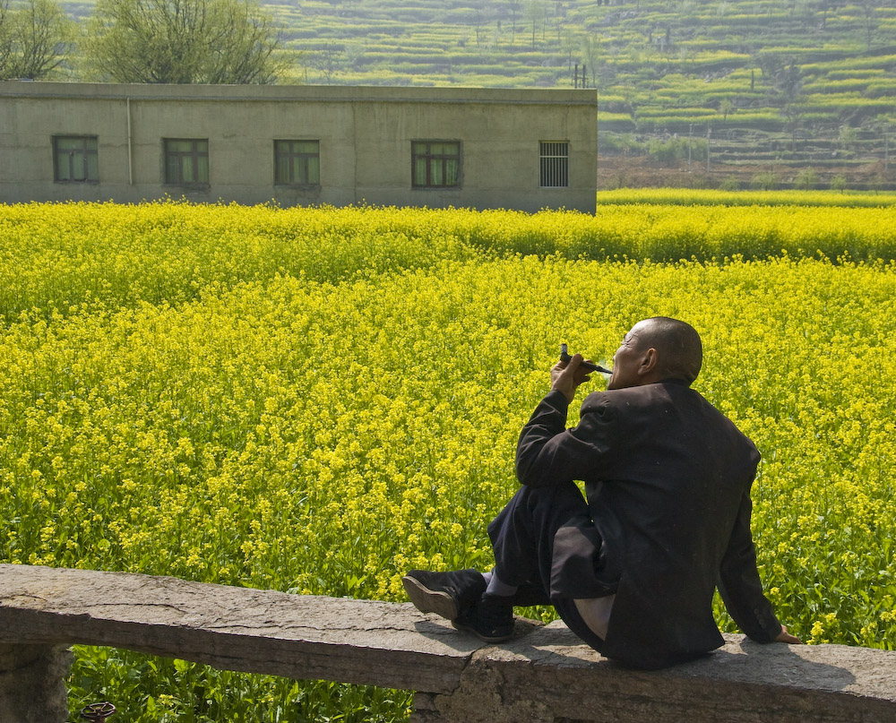 Man smoking his pipe, basking under the sun, Guangxi, China