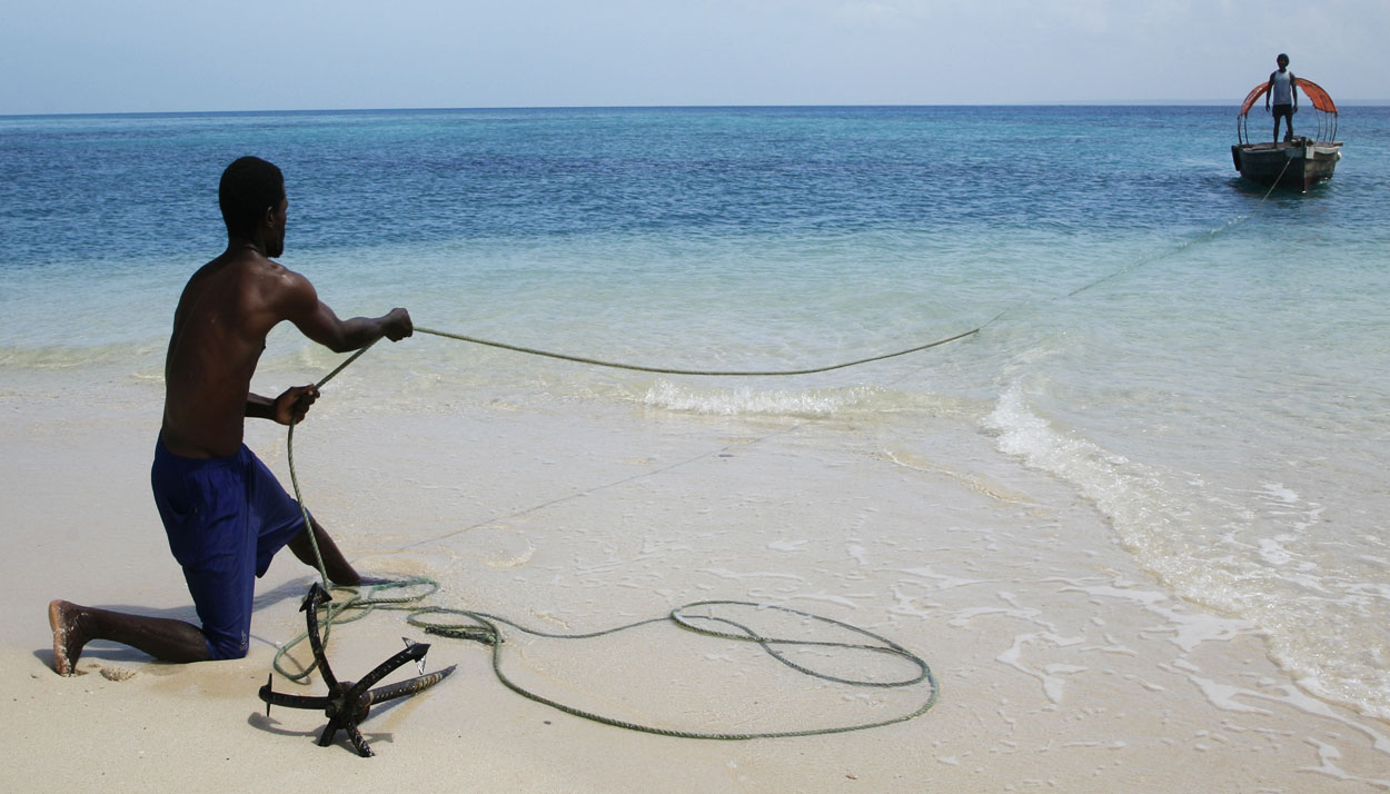 Fisherman pulling in the boat on the beach of Zanzibar